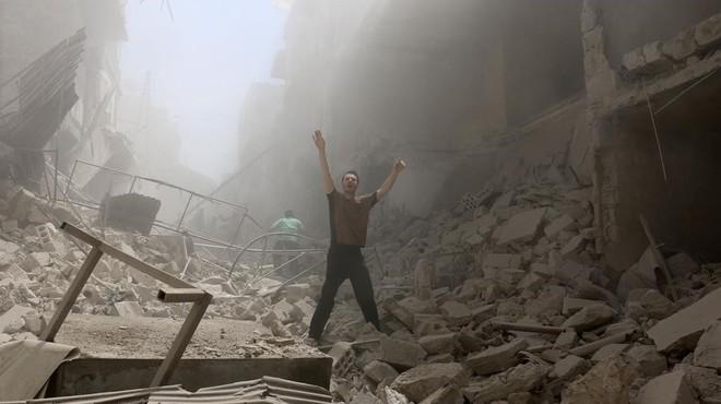 Un hombre pide ayudaen medio de los escombros de los edificios destruidos en una calle de Alepo.