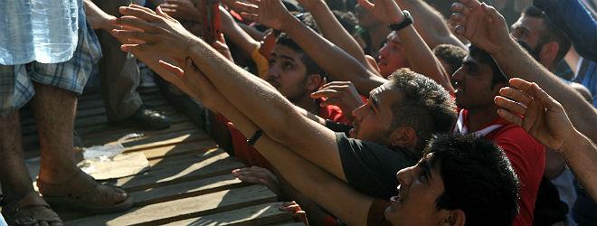 Inmigrantes piden botellas de agua, este viernes, en la frontera de Macedonia y Grecia.