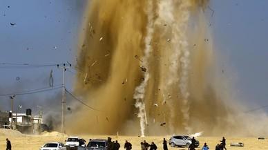 Palestinos corren a refugiarse tras un ataque aéreo israelí en un puesto de Hamas en el norte de la Franja de Gaza.