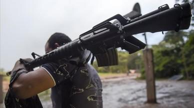 Un miembro de las FARC entrega un fusil de asalto.