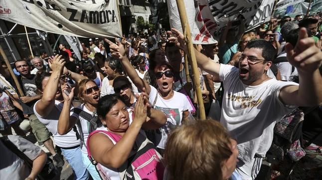 Un grupo de personas se manifiestan en el centro de Buenos Aires, en protesta por los despidos masivos de trabajadores estatales, este miércoles.
