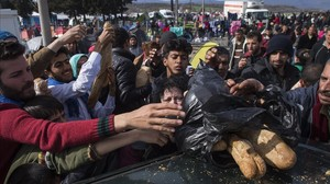 Refugiados que intentan entrar en Macedonia intentan hacerse con pan que reparte una voluntaria en el campo de refugiados cerca de Idomeni.