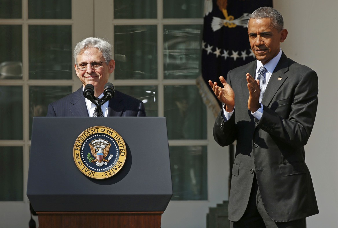 Judge Merrick Garland speaks at the podium in front of U.S. President Barack Obama in Washington