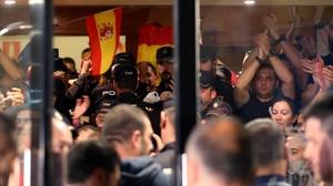 Policías nacionales, en la entrada del hotel de Pineda en el que están alojados, se enfrentan a los ciudadanos que protestan fuera.