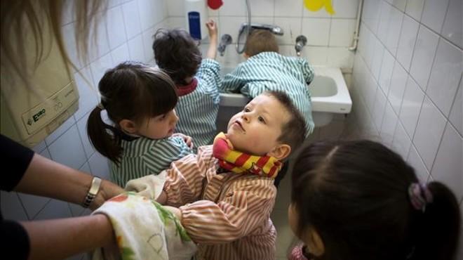 Una profesora ayuda a secarse las manos a sus alumnos de educaci�n infantil antes de ir a comer.