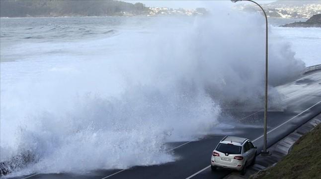 Una gigantesca ola se adentra en la carretera de acceso a la localidad pontevedresa de Baiona.