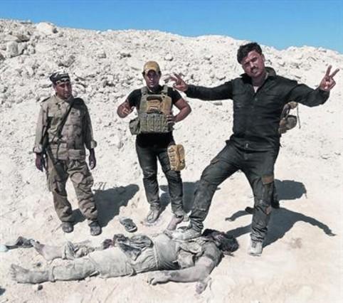 Militares iraquís y milicianos sunís posan con el cadáver de un miembro del Estado Islámico.