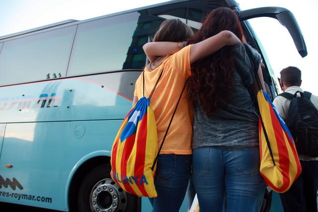 Dos jóvenes con estelades se disponen a subir a un autocar rumbo a Barcelona, esta mañana en Valencia.