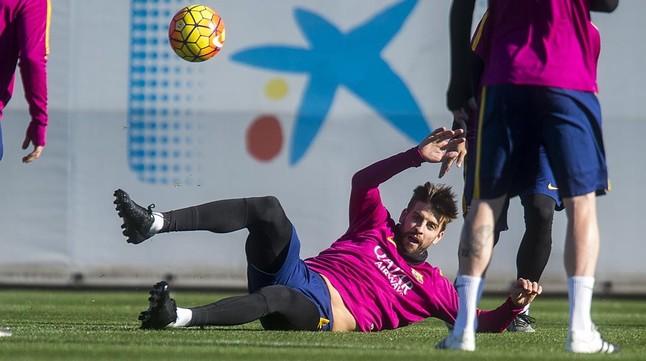 Piqué persigue el balón en el rondo durante el entrenamiento del Barça previo al duelo contra el Granada.