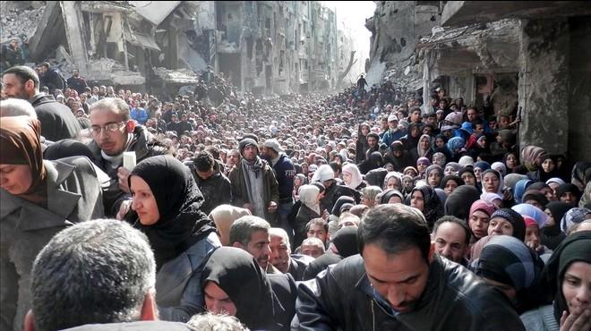 Palestinos refugiados del campo de Yarmouk, en Siria, hacen cola en enero del 2014 para recibir alimentos.