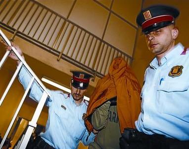 Dos mossos trasladan a uno de los detenidos, en el 2009.