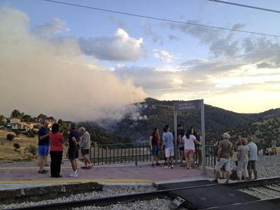 Varias personas miran desde la vía del tren el incendio de Valdemaqueda y Robledo de Chavela, cerca de Madrid.