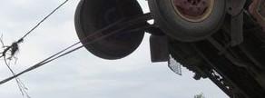 Un hombre intenta poner de pie un camión usando cuerdas en Pakistan.