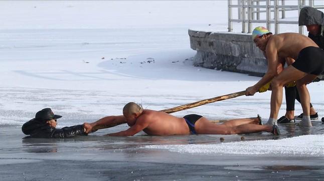 Tres bañistas intentar rescatar a un hombre que ha caído en el lago heladode Chagchun, China.