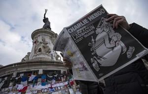 Un lector con el último Charlie Hebdo en la plaza de la República.