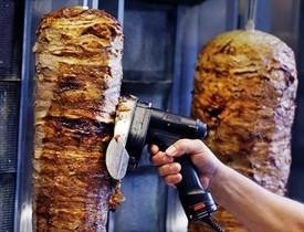 Un hombre corta carne de kebab en un establecimiento de Fráncfort.