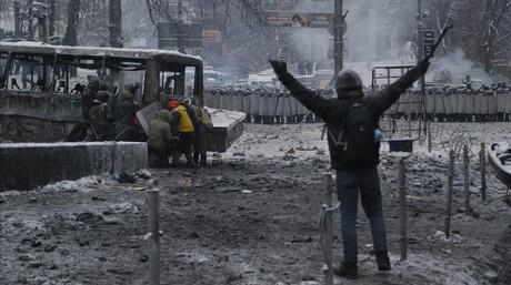 Un manifestante gesticula mientras otros se esconden de la policía detrás de un autobús incendiado, este miércoles en Kiev.