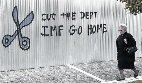 Una mujer pasa ante una pintada contraria a pagar la deuda en Atenas.