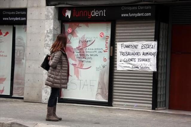 Una joven mira las pancartas de protesta en la fachada de la clínica dental que Funnydent tenía en Mataró.