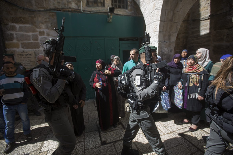 Agentes de policía israelíes caminan junto a un grupo de mujeres palestinas en Jerusalén.