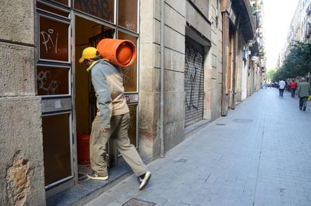 Un hombre entra con una bombona de butano en una vivienda en el Raval.