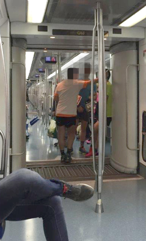 Maratonianos con dorsal por el metro de Barcelona durante la prueba