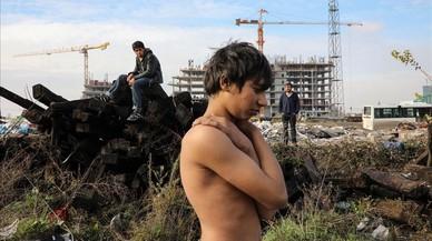Un migrant es prepara per banyar-se, en un magatzem duaner abandonat a Belgrad.