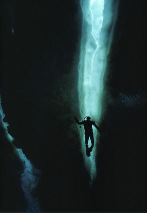 La silueta de un buzo mientras frente a una pared de hielo en la Antartida.