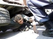 Inmigrante oculto en los bajos de un camión.