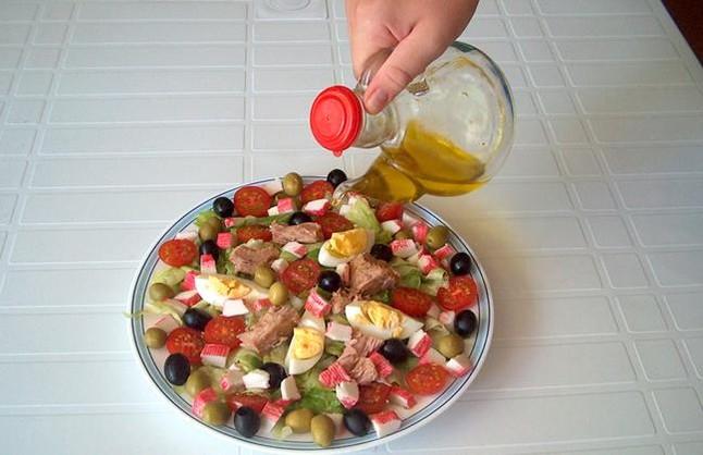 Aliño de una ensalada con una aceitera.