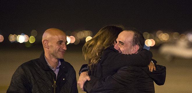 Marc Marginedas rep l'abraçada de la seva germana davant la mirada del seu germà a l'aeroport del Prat.
