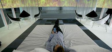 Un usuario prueba la habitaci�n de hotel inteligente, que maneja con su m�vil.