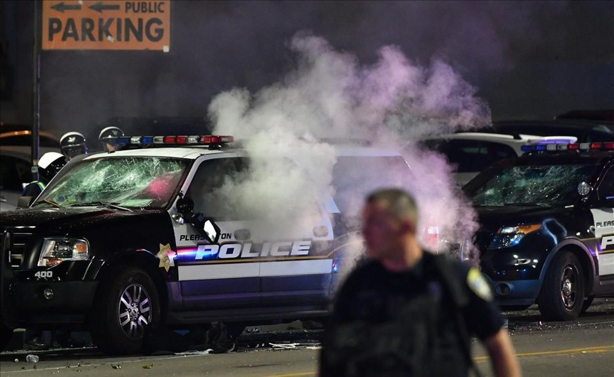 Creman un coche policial durante las protestas en contra de Trump