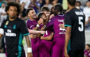 Los jugadores del City celebran un gol ante la mirada de Marcelo y Varane