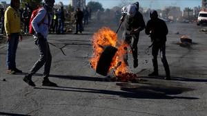 Manifestantes palestinos queman un neumático en protesta por la decisión de EEUU, en Ramalá, este martes 26 de diciembre.