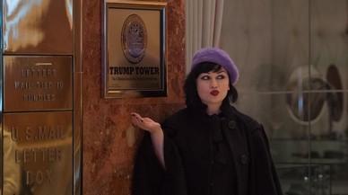 Una mujer posa anteun letrero en la entrada de la Torre Trump en la Quinta Avenida de Nueva York.