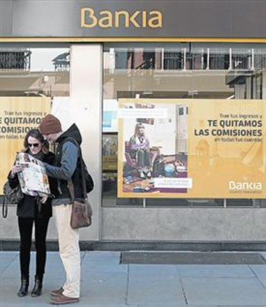 Unos turistas en Sevilla, ante una sede de Bankia.