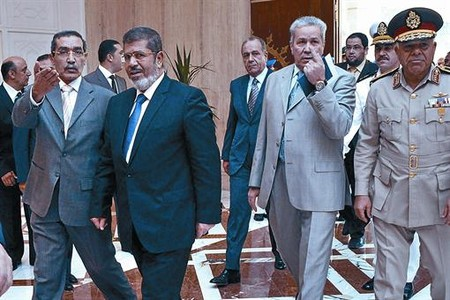 El presidente electo, Mohamed Morsi, se adentra junto a funcionarios y militares en el palacio presidencial egipcio, ayer.