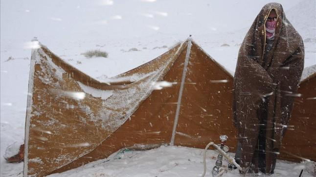 Un hombre se protege del frío durante una insólita nevada en Arabia Saudí.
