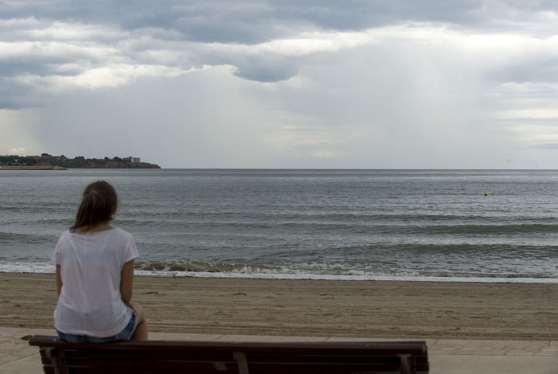 Una mujer mira el cielo que amenaza lluvia en la playa del Arenal, en LAmpolla (Baix Ebre).