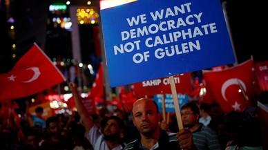 Un hombre sostiene un cartel junto a otros reunidos noche tras noche desde el 15 de julio, d�a del intento de golpe de Estado, en Ankara, el 27 de julio.