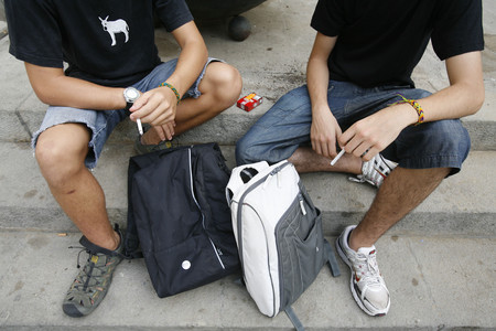 Dos adolescentes de 15 años fumando un cigarrilo.