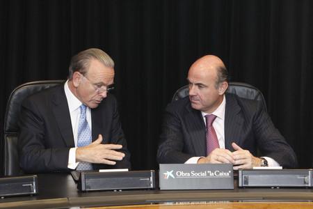 El presidente de La Caixa, Isidre Fainé, y el ministro de Economía, Luis de Guindos, el pasado octubre, durante la firma de un convenio sobre un nuevo programa de becas.