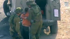Dos soldados israel�s detiene a un ni�o palestino el 19 de octubre en Hebr�n.