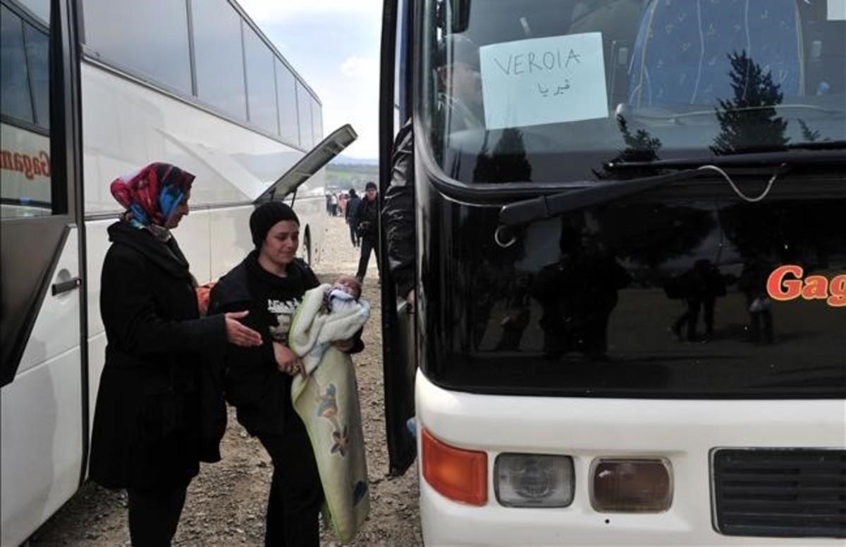Dos mujeres se disponen a subir a un autocar en el campamento de Idomeni.