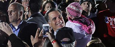Romney sostiene en brazos a una niña, durante un mitin en Ohio. REUTERS