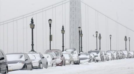 Coches cubiertos de nieve en el puente Washington de Manhattan.