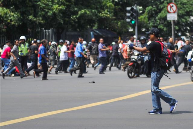 Un hombre armado apunta hacia un centro comercial mientras decenas de personas corren, en el centro de Yakarta.