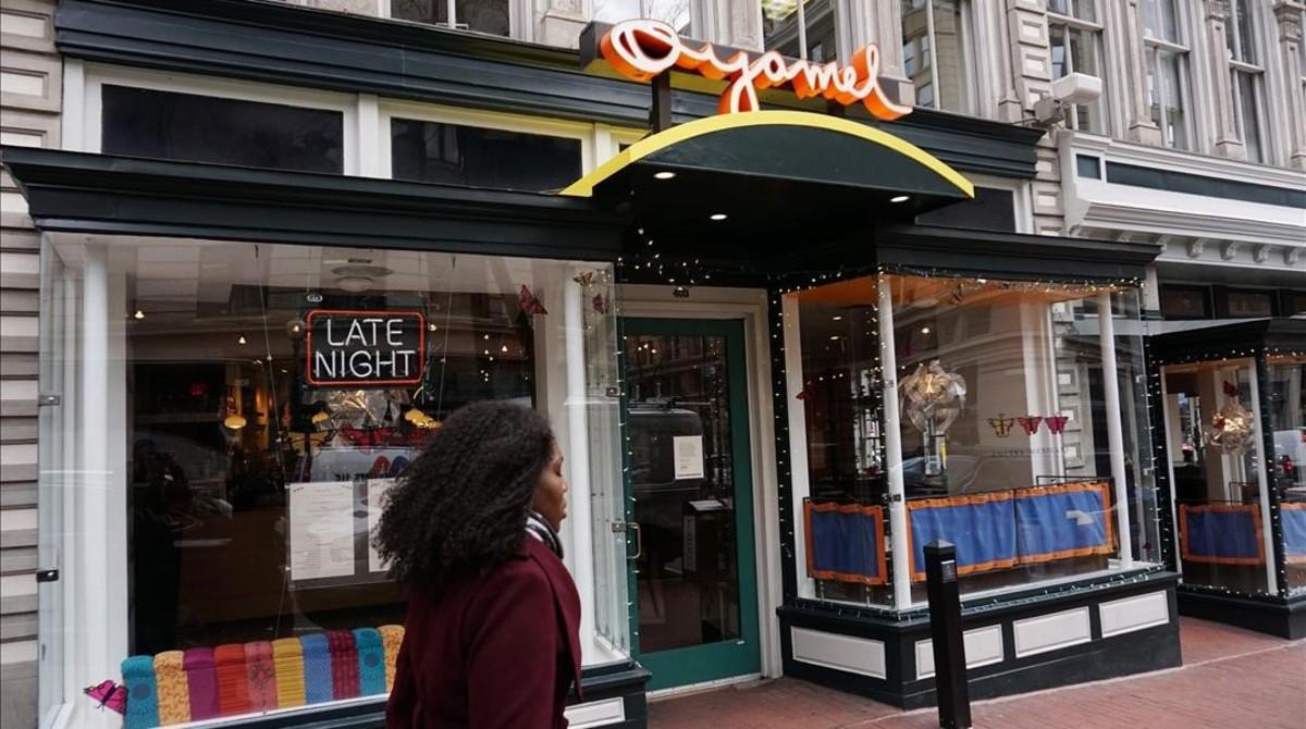 Una mujer pasa junto a un restaurante cerrado por el Día sin Inmigrantes, en Washington, este jueves.
