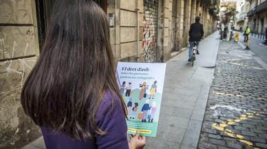 Irina, en una calle del Raval, contempla un cartel en el que se reflexiona sobre la situación de los refugiados.